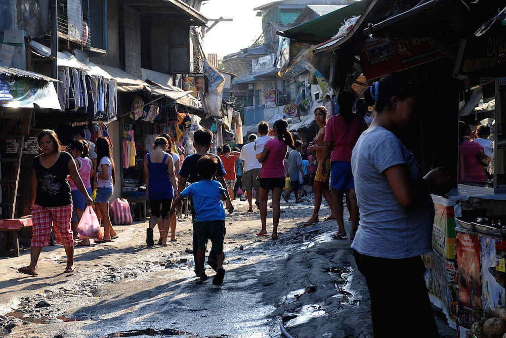 Philippine residents walks the street in one of the shanty towns in Manila on April 8, 2011. At night, these children sleep in the street under a sheet of canvas. A survey by a respected research group found that the number of people who considered themselves poor and hungry had risen under the administration of President Benigno Aquino. The president however expressed disbelief over the survey, saying it did not fully cover his efforts to create jobs to help the poor.   AFP PHOTO / JAY DIRECTO (Photo credit should read JAY DIRECTO/AFP/Getty Images)