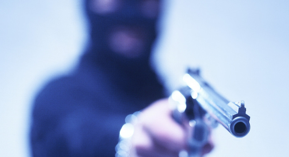 blurred view of a person wearing balaclava and aiming  with a pistol  in his hand